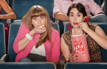 13992462 - two amazed women eating popcorn in a theater